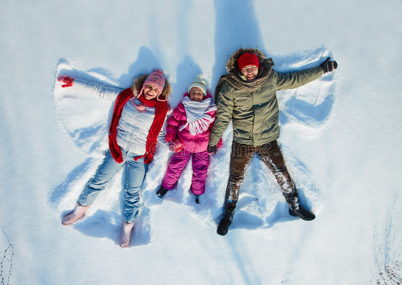 Family in snow. Happy family of three having fun in snowdrift stock images
