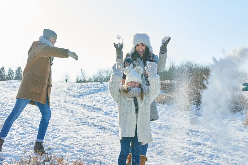 Family in snowball fight having fun stock photo