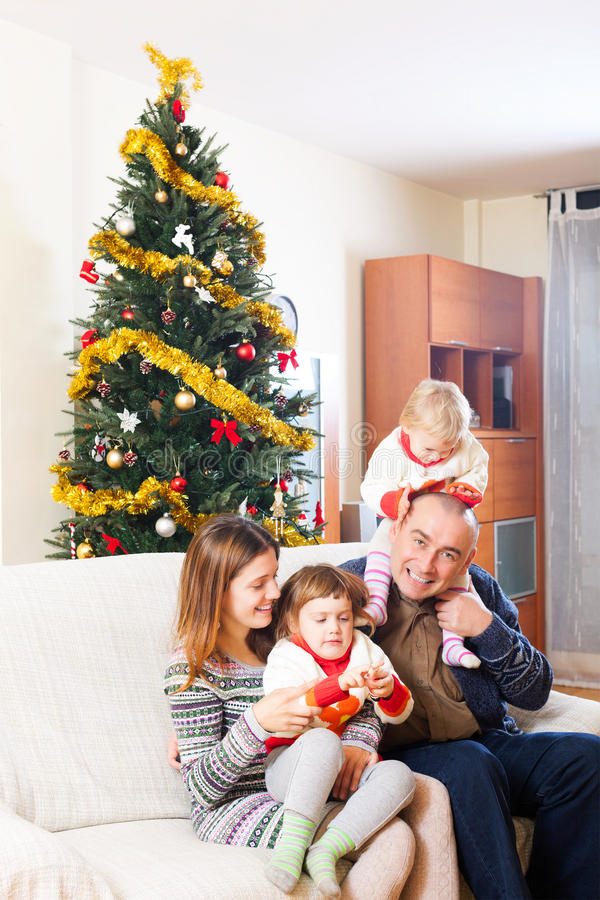 Family on sofa at christmas. Happy family of four celebrating Christmas in living room royalty free stock image
