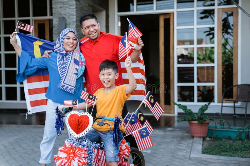 Family and son celebrating malaysia merdeka or malaysian independence day. By decorating bicycle at home together royalty free stock images