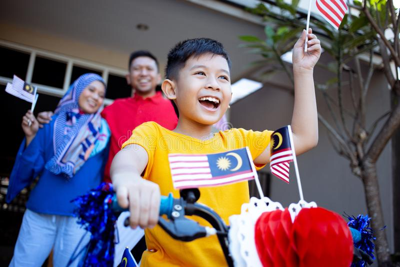 Family and son celebrating malaysia merdeka or malaysian independence day. By decorating bicycle at home together royalty free stock photography