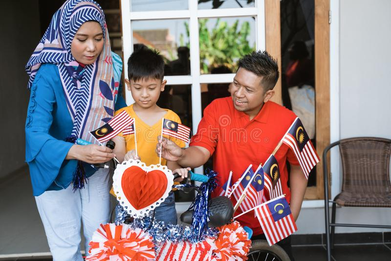 Family and son celebrating malaysia merdeka or malaysian independence day. By decorating bicycle at home together royalty free stock photo