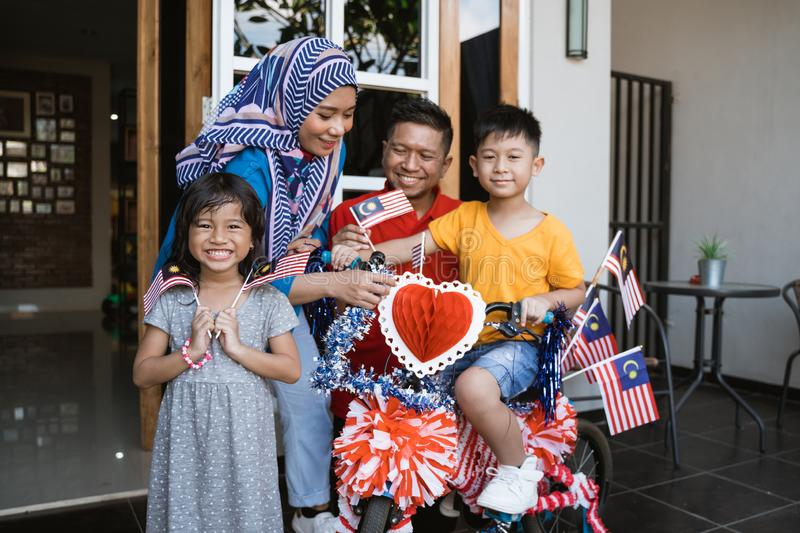 Family and son celebrating malaysia merdeka or malaysian independence day. By decorating bicycle at home together stock image