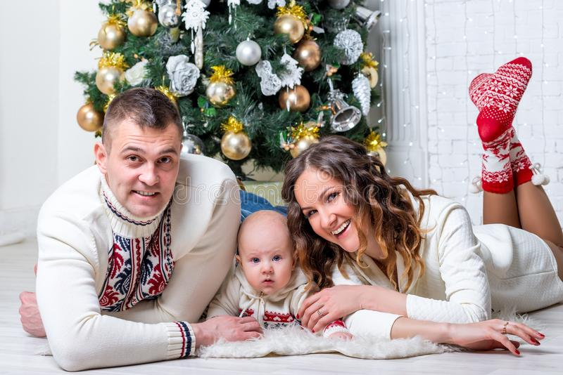 Family with son near New Year`s fir tree posing and lying stock photos