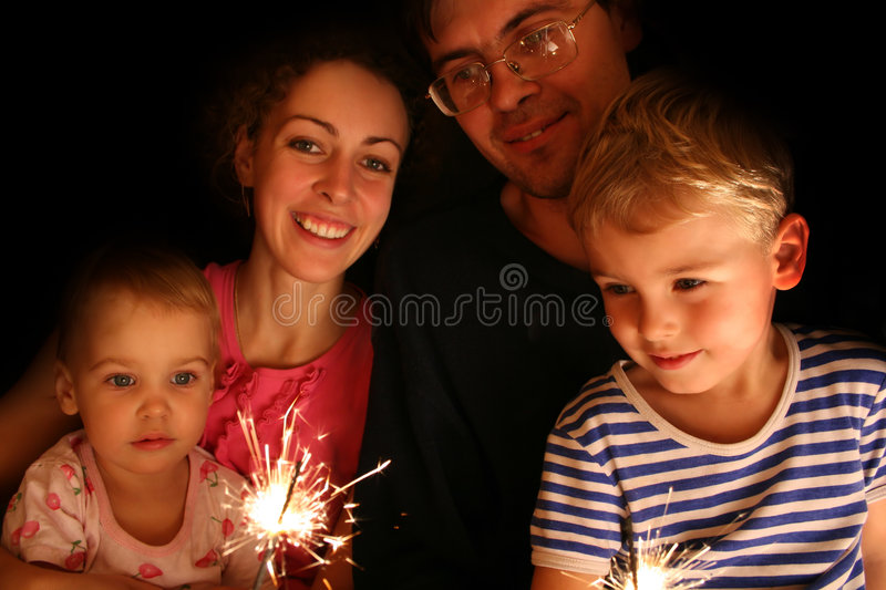 Family with sparkler. Family of four with sparkler