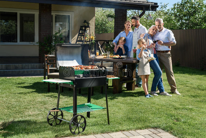 Family spend time together while having barbecue with grill at yard. Happy family spend time together while having barbecue with grill at yard royalty free stock photos