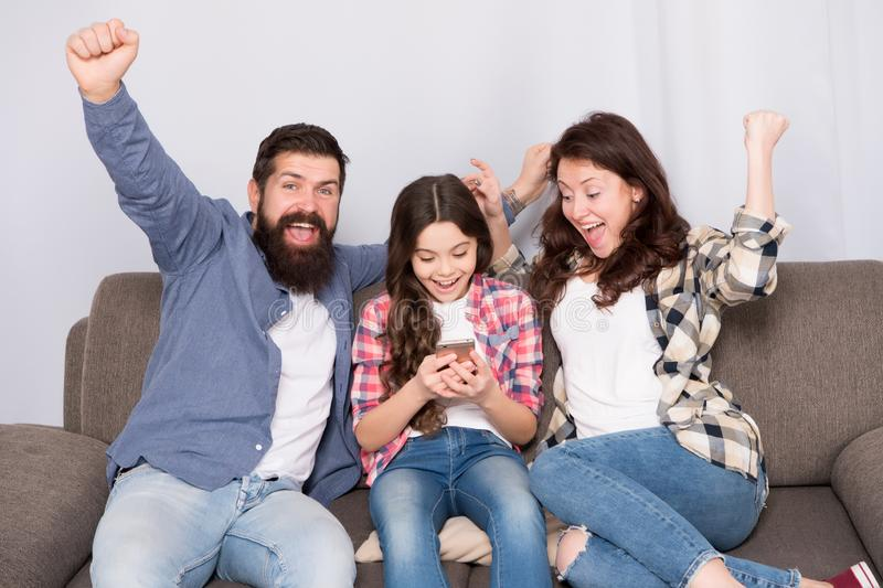 Family spend weekend together. Child little girl use smartphone with parents. Friendly family having fun together. Mom royalty free stock photos