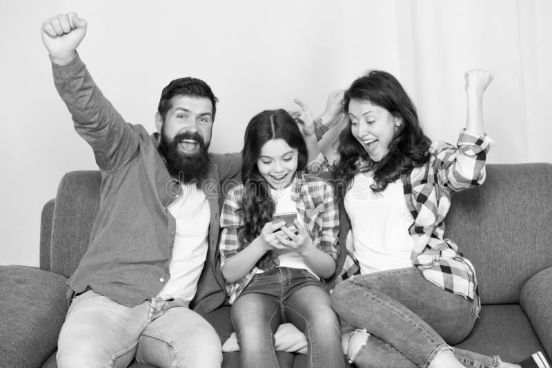 Family spend weekend together. Child little girl use smartphone with parents. Friendly family having fun together. Mom stock photo