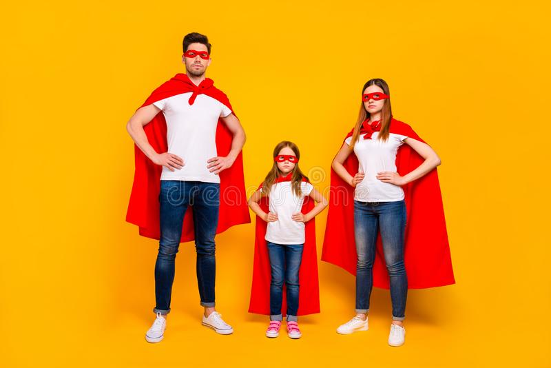 Family spending leisure time playing cartoon characters wear superhero costume isolated yellow background. Family spending leisure, time playing cartoon royalty free stock image