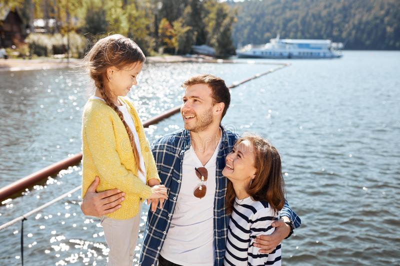 Happy family spending time together outside near lake. Parents playing with daughter hugging and having fun. Family spending time together outside near lake royalty free stock photography