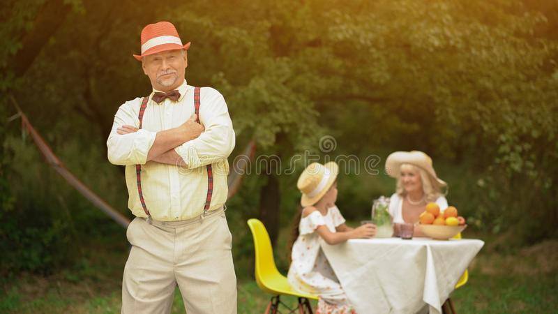 The Portrait Of A Family Resting Together in The Garden. The family spends free time in the countryside.The men is posing with crossed arms.Granny and stock image