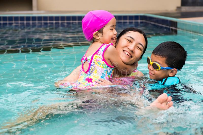 Family spent time to swim in swimming pool. they enjoy playing t royalty free stock images