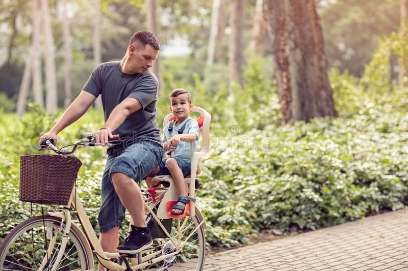 Family sport and healthy lifestyle- father and son riding a bicycle together outdoors in a city park. stock image