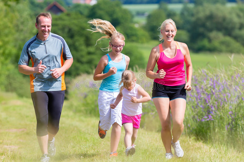 Family sport running through field. Parents with two children sport running outdoors royalty free stock photography