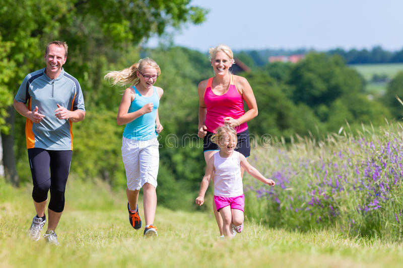 Family sport running through field. Parents with two children sport running outdoors stock image
