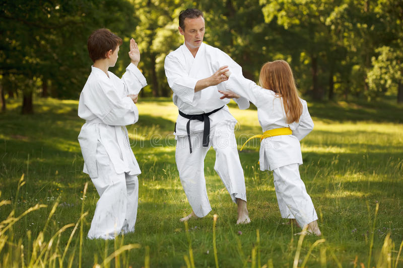 Family sports. Family exercising martial arts in forest
