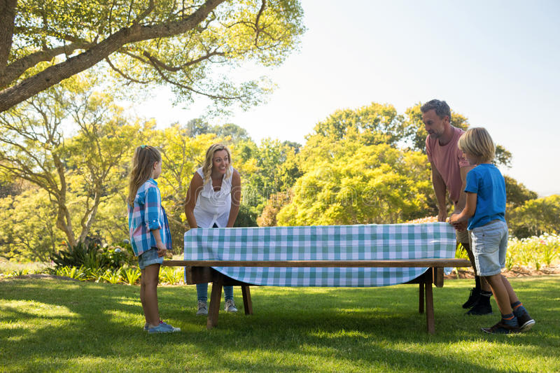 Family spreading the tablecloth on picnic table. In park stock images