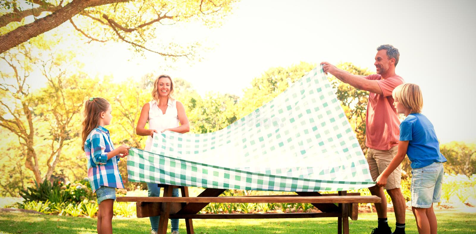 Family spreading the tablecloth on picnic table royalty free stock photography