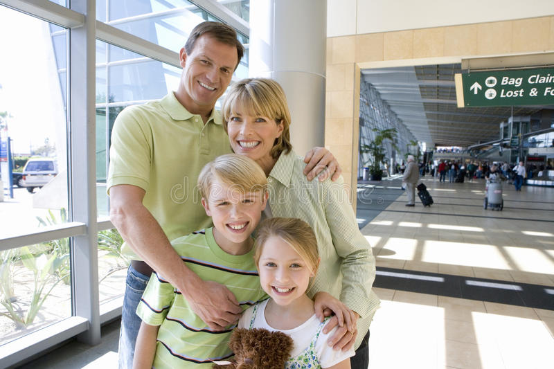 Family standing in airport, smiling, front view, portrait stock image