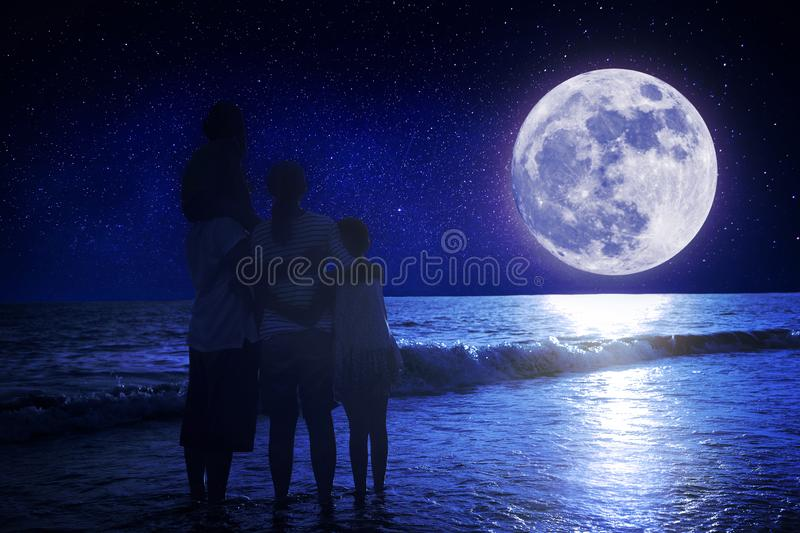 Family standing on beach and watching the moon.Celebrate Mid-autumn festival royalty free stock photography