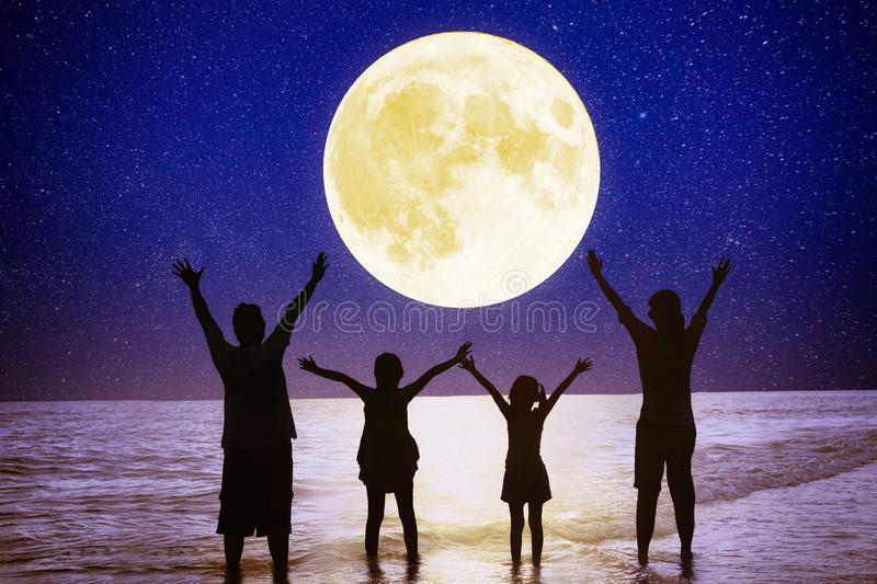 Family standing on beach and watching the moon.Celebrate Mid autumn festival royalty free stock images