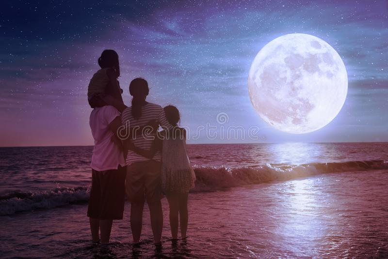 Family standing on beach and watching the moon.Celebrate Mid-autumn festival. Together stock image