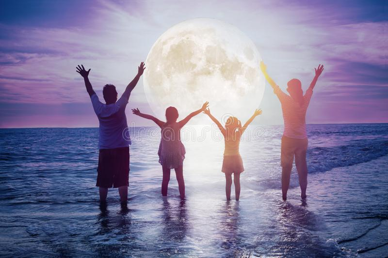 Family standing on beach and watching the moon.Celebrate Mid-autumn festival. Together stock photography