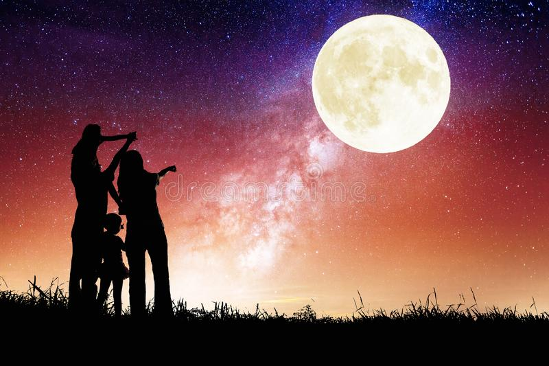 Family standing on hill and watching the moon.Celebrate Mid-autumn festival stock photo