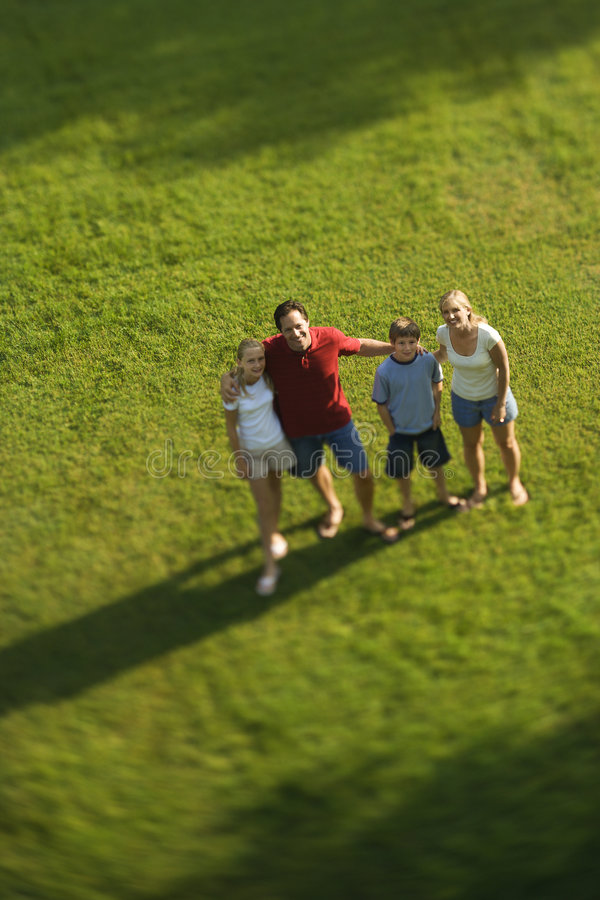Family standing on lawn. stock photos