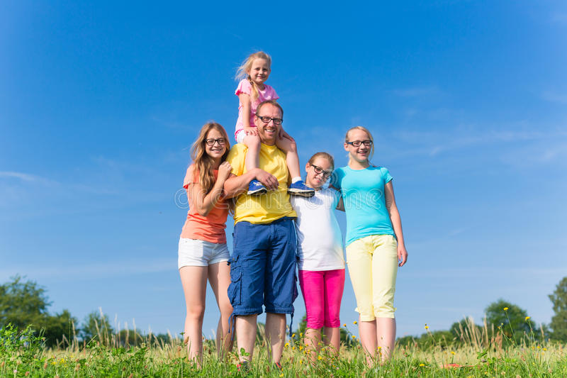 Family standing on meadow - father with children. In grass stock image