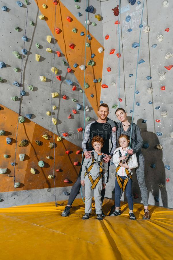 Family with children standing together near climbing walls at gym and looking. At camera royalty free stock photography
