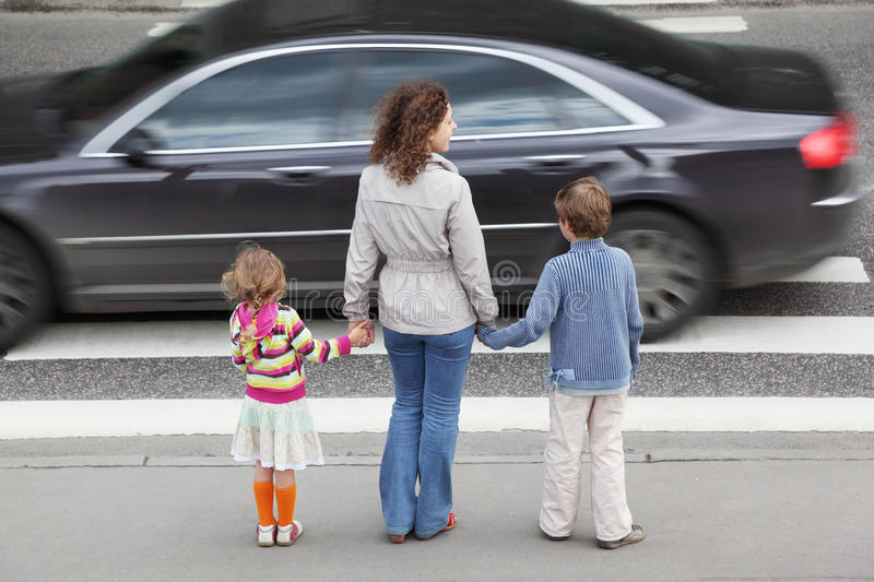 Family standing near cross road, behind stock photography