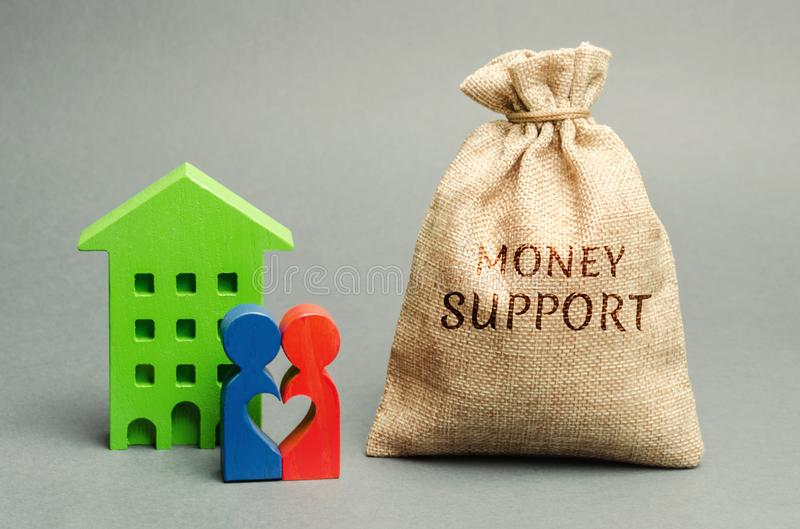 Family standing near the house with a bag with the word Money support. Financial assistance to support young families. Stimulating stock photos