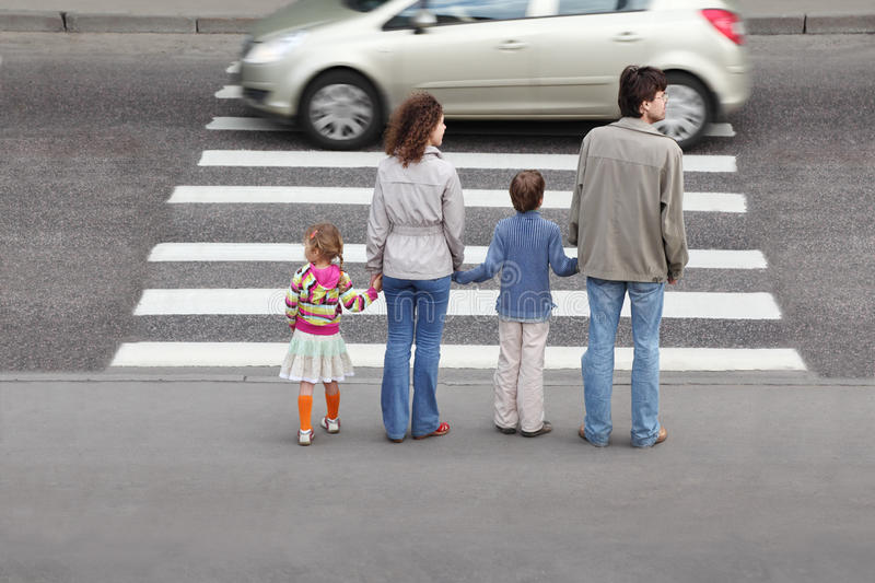Family standing near pedestrian crossing. Mother and father holds hand of little daughter and son and standing near pedestrian crossing, behind, car on road