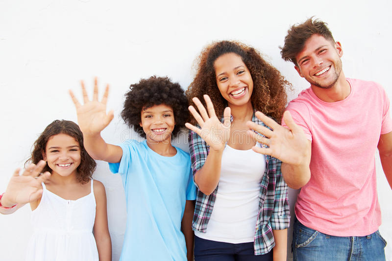 Family Standing Outdoors Against White Wall And Waving royalty free stock image