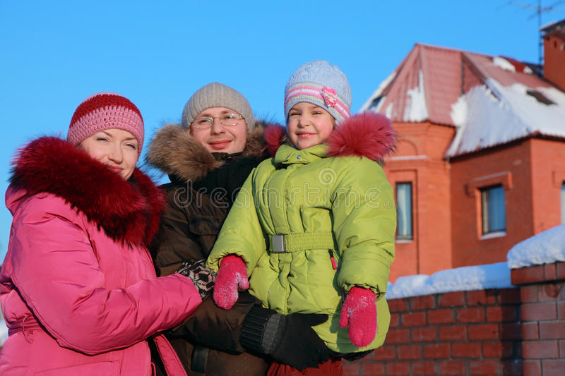 Family standing outdoors in winter near house stock photos