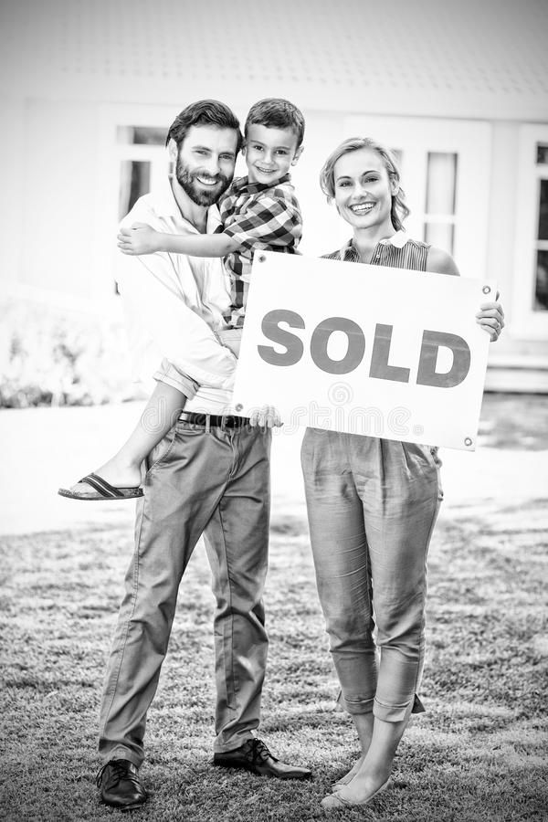 Family standing outside home with sold sign stock photos