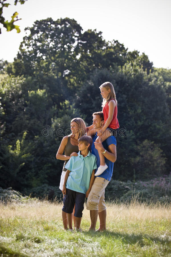 A family standing in a park, father carrying his daughter on his shoulders stock photo