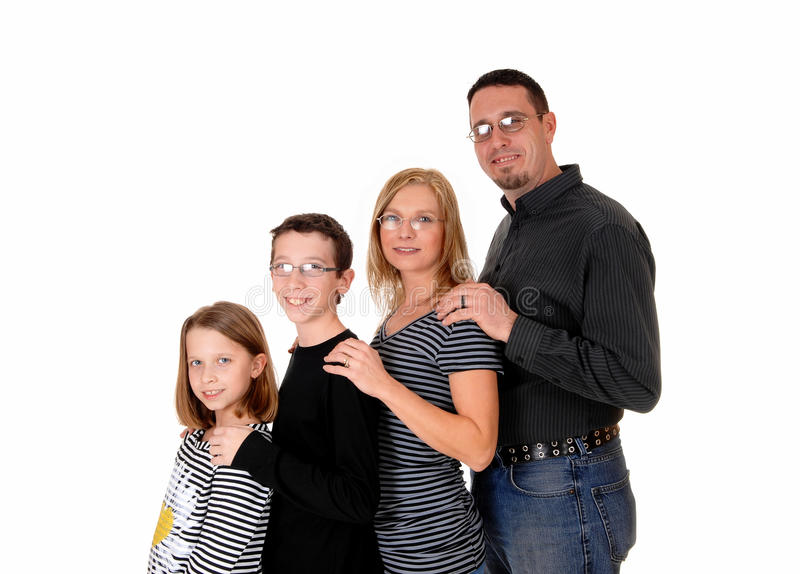Family standing in profile. A young family wit two kids standing in profile in frond of each other, isolated on white background royalty free stock image