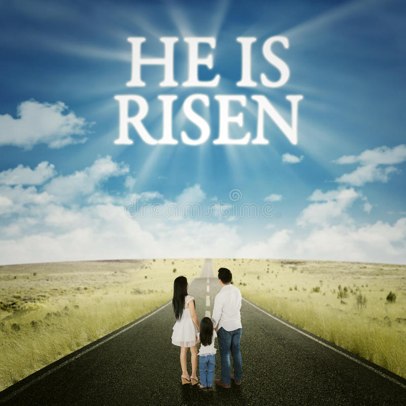 Family standing on the road with text he is risen. Rear view of happy family standing on the road with text he is risen on the sky stock photos