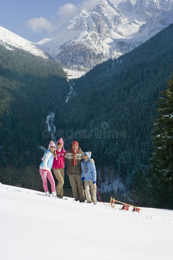 Family standing in snow with sled with mountain in background royalty free stock photography