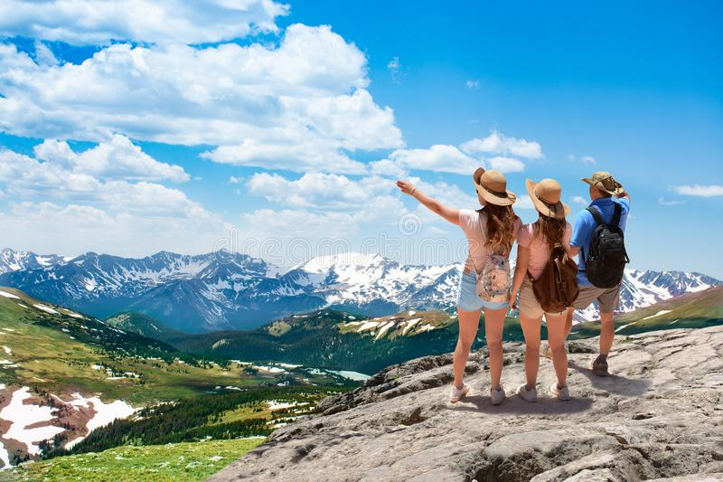 Family standing on top of the mountain looking at beautiful view. Early summer landscape with green meadows and snow covered mountains. Trail Ridge Road. Rocky stock photos