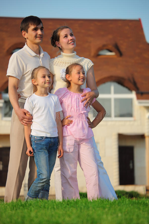 Family stands on grass against house. Family from four stands on grass against house stock image
