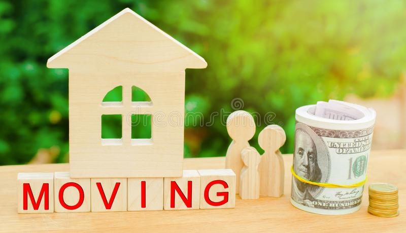 Family stands near the miniature house with money and the inscription `moving`. real estate concept. moving to another apartment,. City or country. dislocation stock images