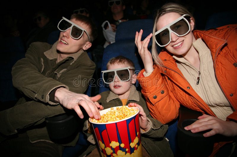 Family in stereo cinema. Focus on popcorn
