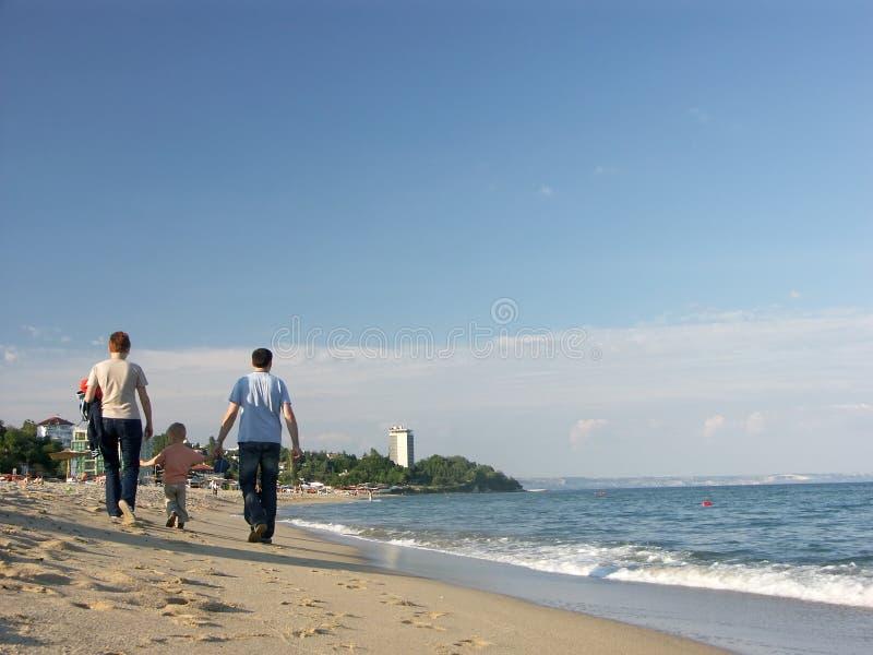 Family stroll along seashore stock image