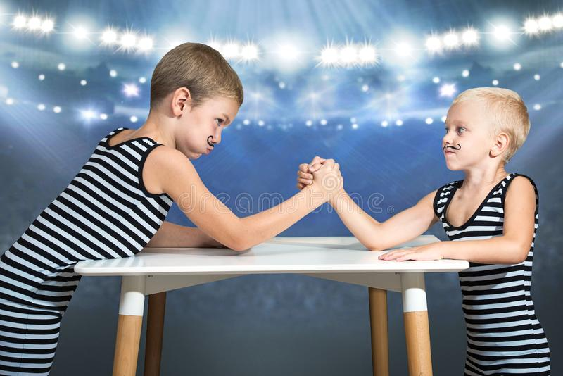 Family of strongman. Brothers in vintage costume of athletes compete in arm wrestling. Family look. Family of strongman. Brothers in vintage costume of athletes royalty free stock image