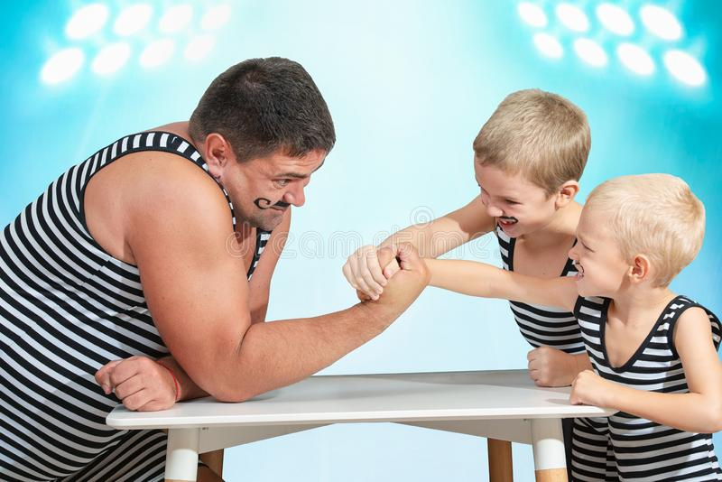 Family of strongman. The father of two sons in vintage costume of athletes compete in arm wrestling. Family look. Family of strongman. The father of two sons in stock images