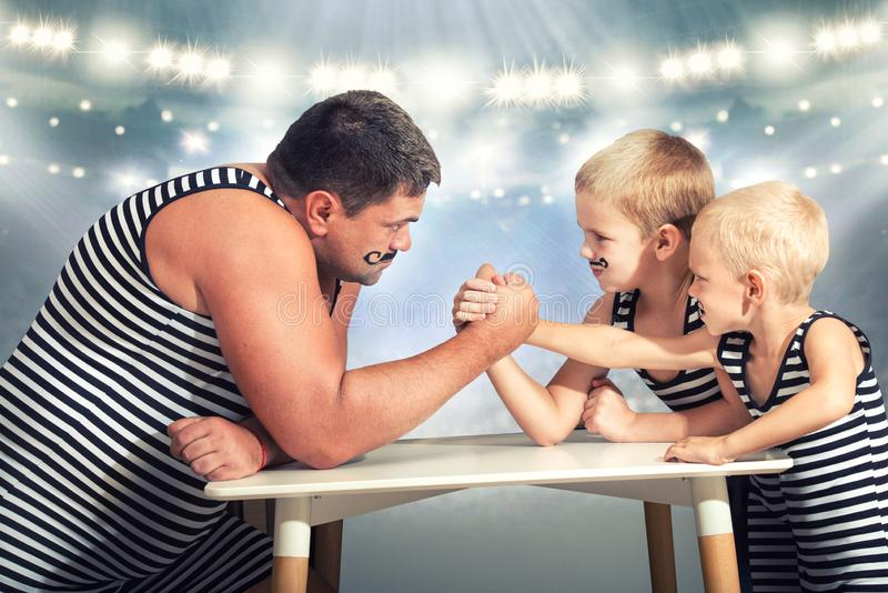 Family of strongman. The father of two sons in vintage costume of athletes compete in arm wrestling. Family look. stock photos