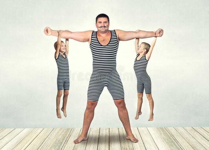 Family of strongman. The father of two sons in vintage costume of athletes perform strength exercises. Family look. stock photography